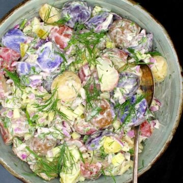 Image of vegan potato salad in a glazed clay bowl with vegan mayo and dill