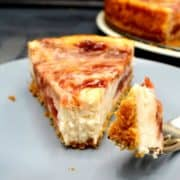 A slice of vegan strawberry rhubarb cheesecake with a morsel on a fork to show the creamy filling.
