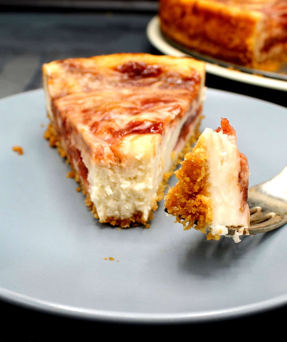 A slice of vegan rhubarb strawberry cheesecake with a morsel on a fork to show the creamy filling.