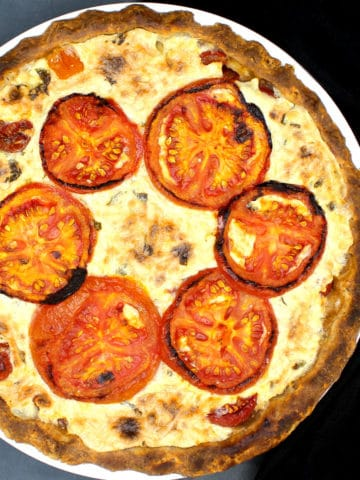Closeup of vegan tomato pie in a white baking dish