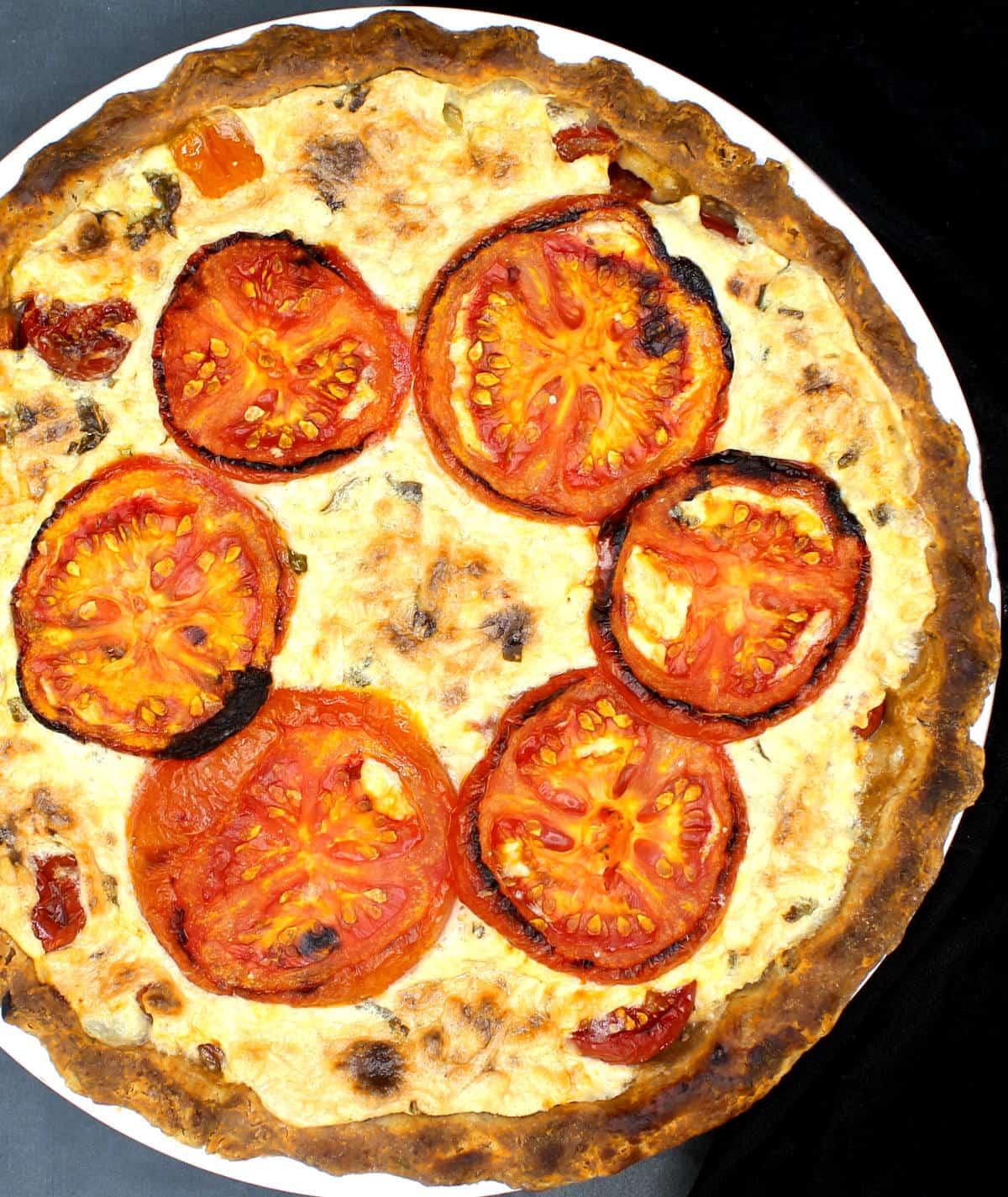 Overhead photo of a vegan tomato pie in white pie plate.