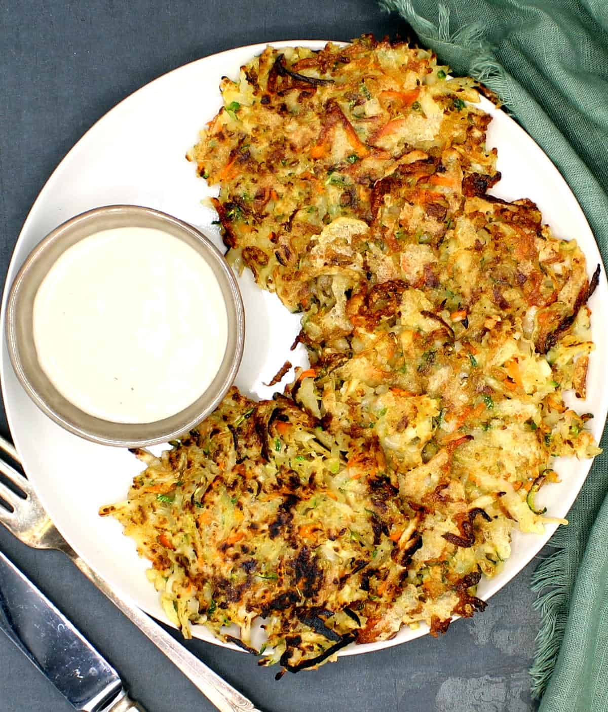 Overhead shot of vegan hash browns with a white sauce in a bowl and a fork and knife on the side with green napkin.