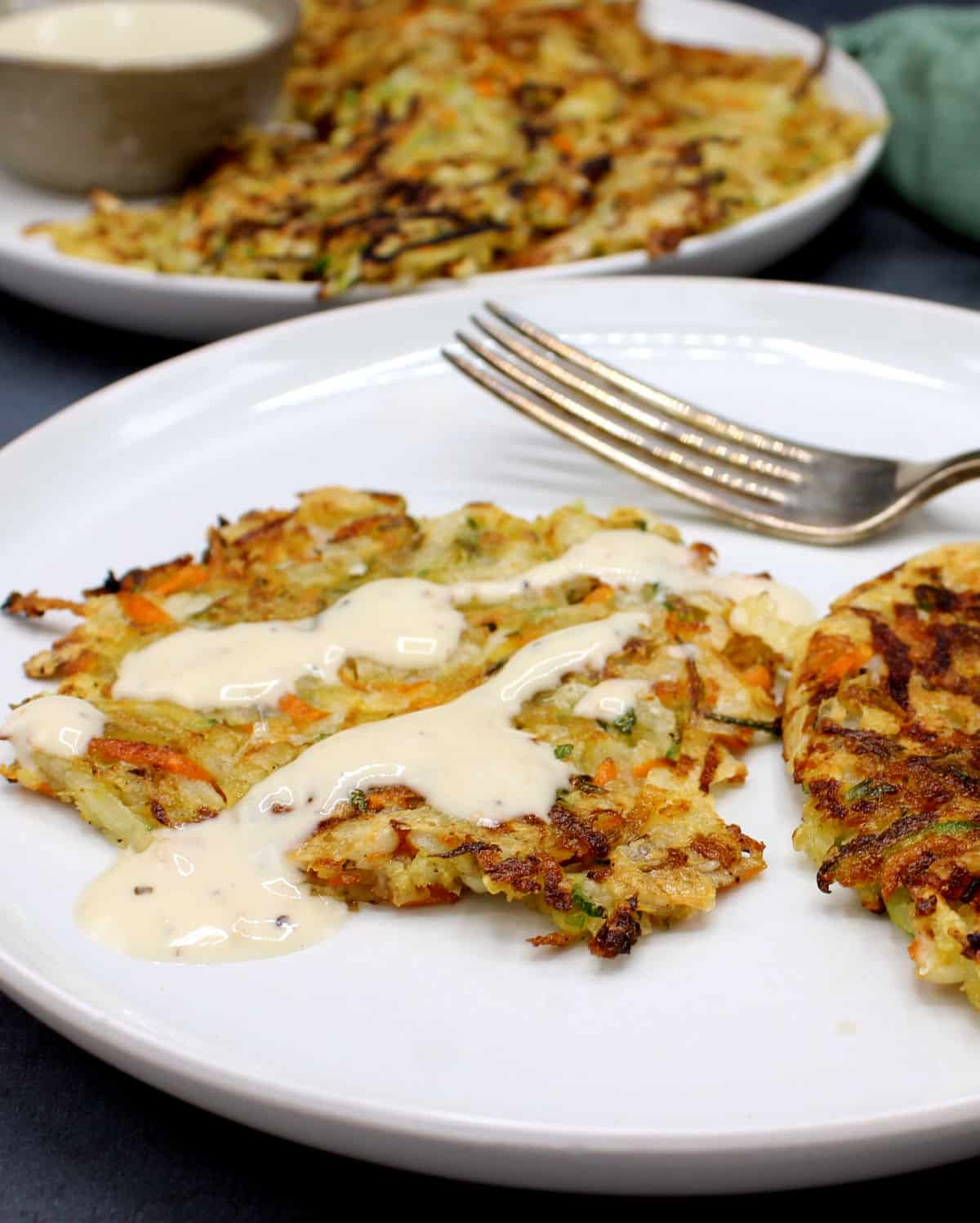 Photo of two vegan hash browns on a white plate with a creamy white sauce with more hash browns in background.