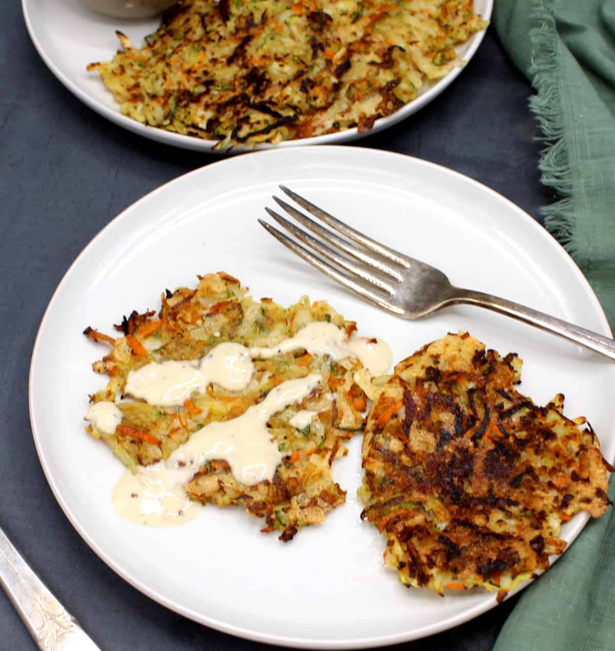 Front photo of two vegan hash browns on white plate with a fork.