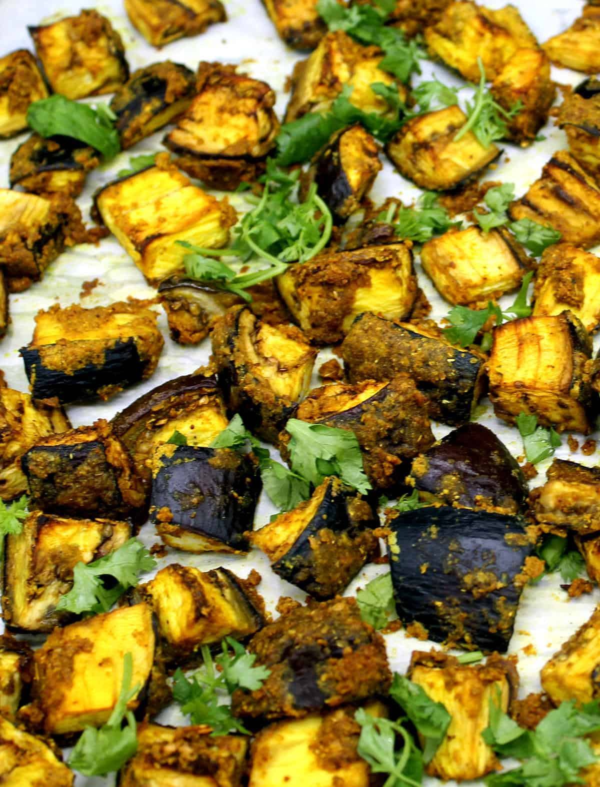 Closeup photo of curry roasted eggplant cubes on a baking sheet with cilantro.