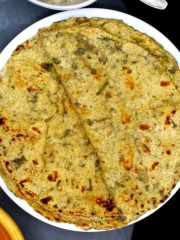 Photo of palak paratha stacked on a white plate