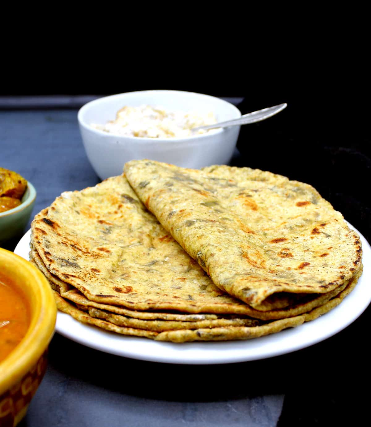 Photo of palak paratha in a white plate with raita and pickles and a dal.