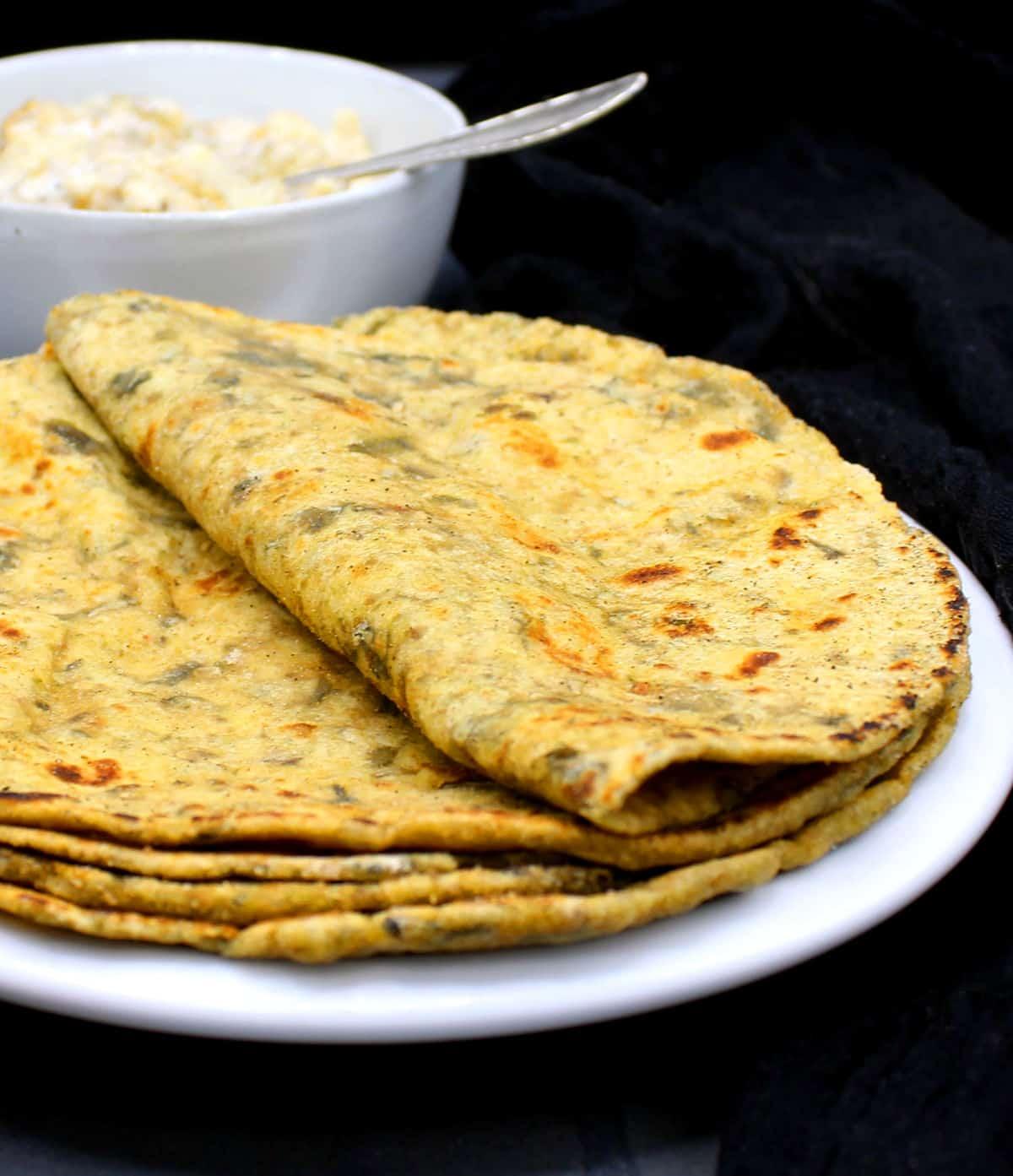 Closeup photo of palak paratha in white plate.