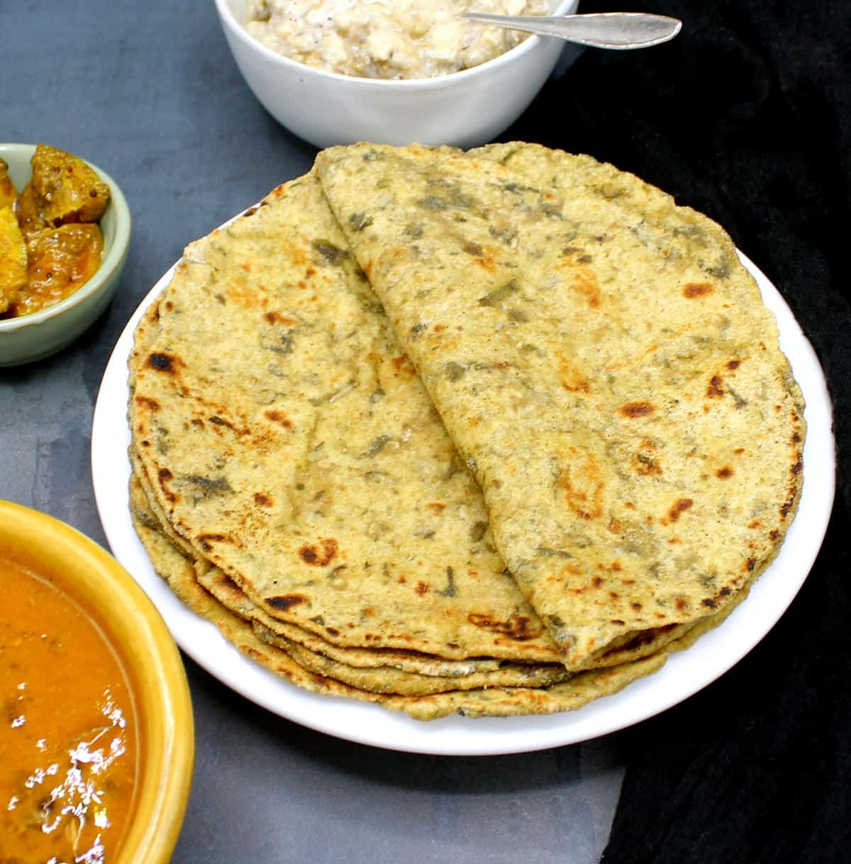 Photo of palak paratha stack served with pickles, dal and raita.