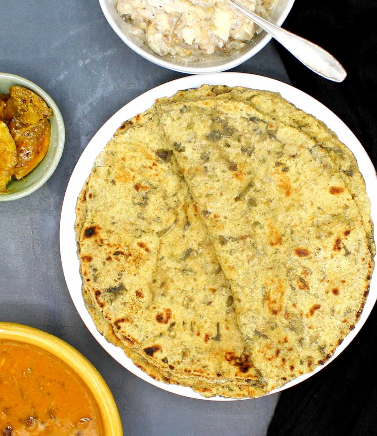 Overhead photo of palak paratha with raita and pickles