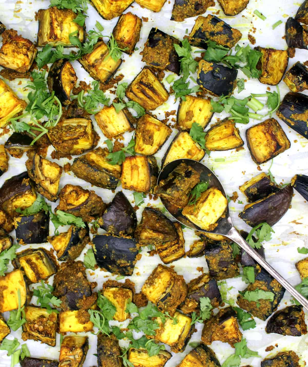 Photo of curry roasted eggplant on baking sheet with spoon.