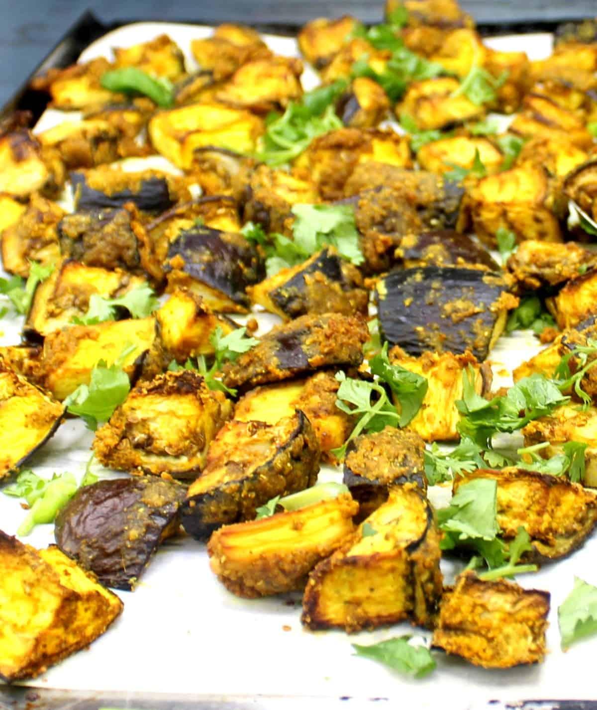 Photo of curry roasted eggplant with cilantro on baking sheet.