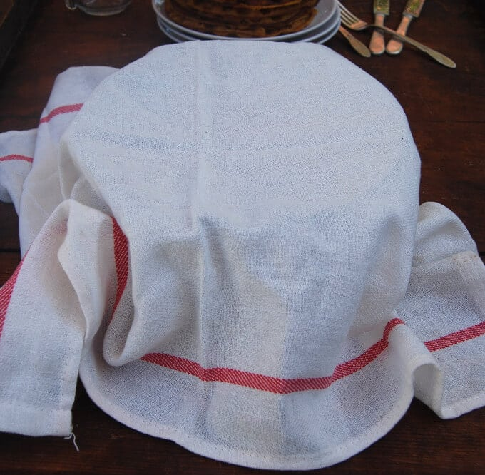 A bowl of sourdough starter covered with a white flour sack cloth with a red border.