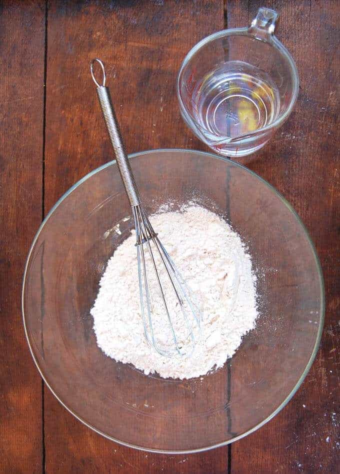 Photo of flour with a whisk in glass bowl with water in a measuring cup on the side to make sourdough starter.