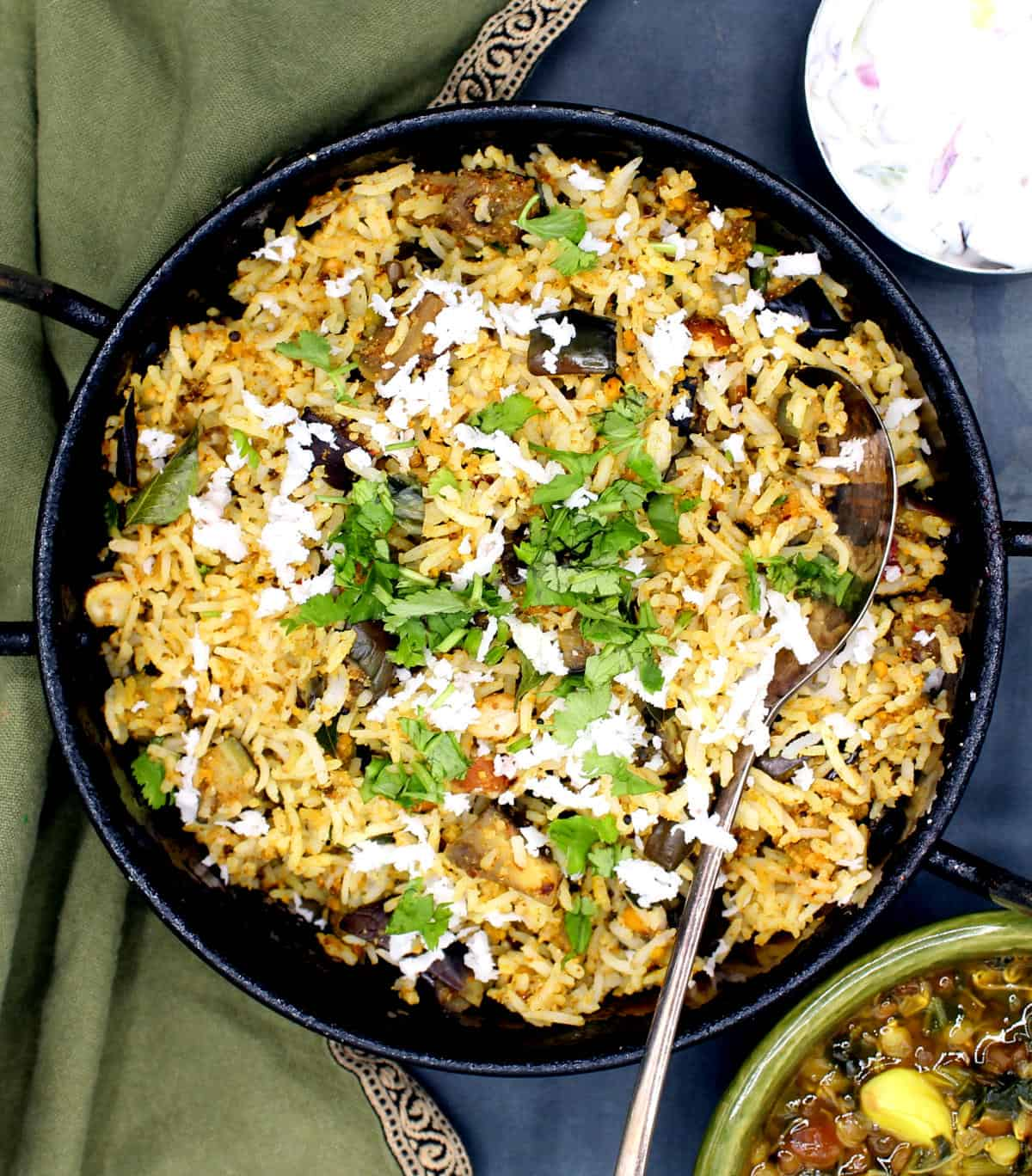 Photo of vangi bath or south Indian eggplant rice served in a steel karahi bowl with cilantro and coconut garnish and raita and dal on the side.