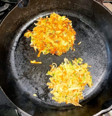 Vegan hash browns cooking on cast iron skillet