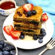 Vegan Sheet Pan Pancake squares on a white plate with strawberries, blueberries, chocolate chips and maple syrup.