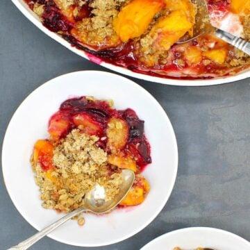 Closeup photo of vegan peach plum crisp in a white bowl with spoon