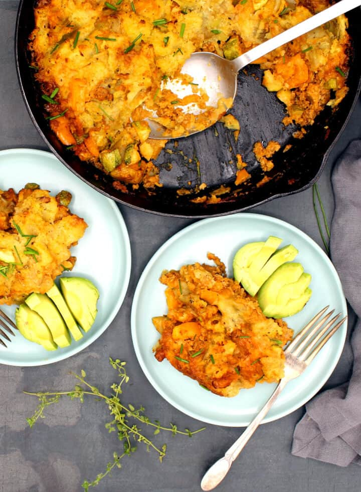 Photo of cheesy vegan dinner pasta bake in skillet and served in two blue-green plates with avocado.