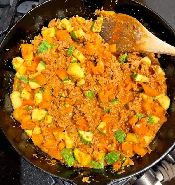 Vegan meat and veggies cooking in cast iron pan