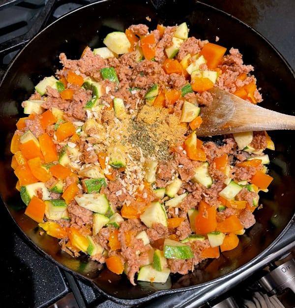 Vegan meat and veggies before seasoning in cast iron pan