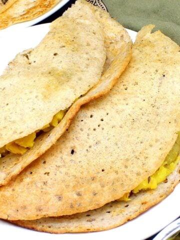 Closeup of two jowar dosas stuffed with potato masala on a white plate.