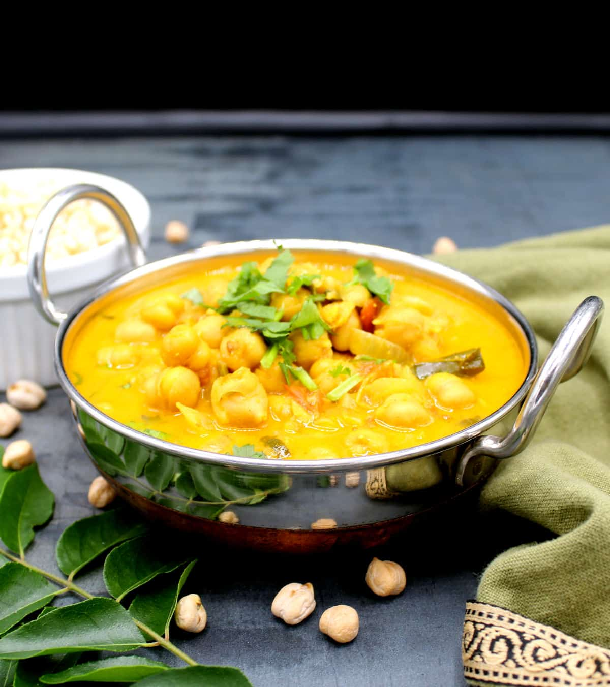 Front photo of chickpea curry with coconut milk in a bowl with chickpeas, curry leaves and brown rice and a napkin.