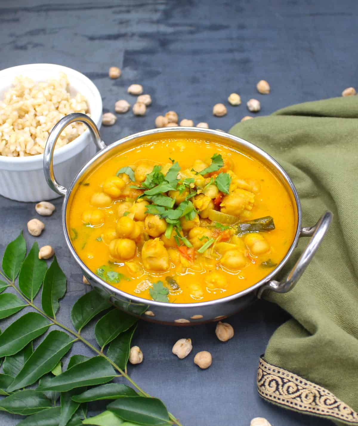 Front photo of a karahi with chickpea curry with cilantro garnish and served with brown rice with chickpeas and curry leaves scattered around.