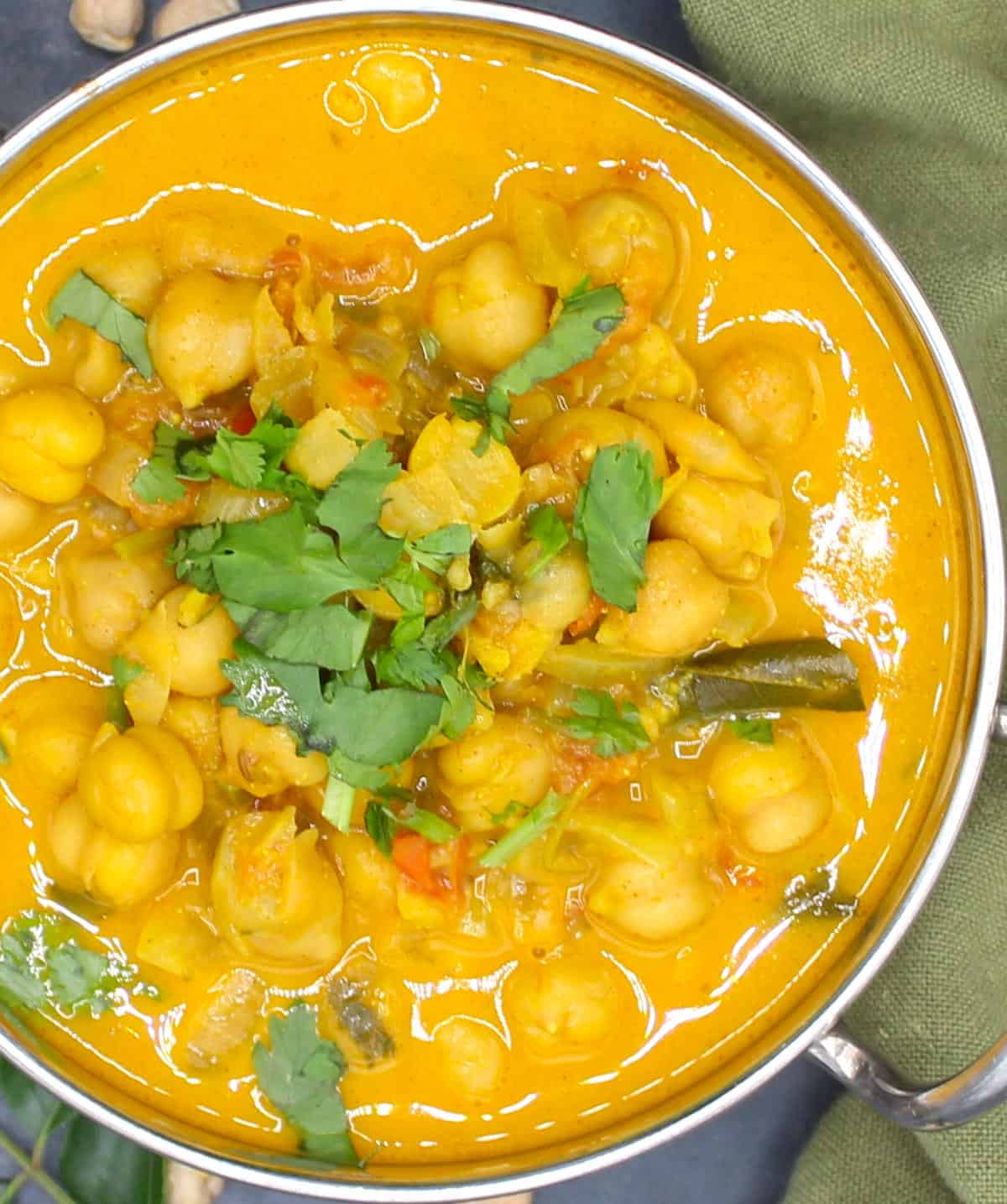 Overhead closeup of a steel bowl of chickpea curry with cilantro garnish.
