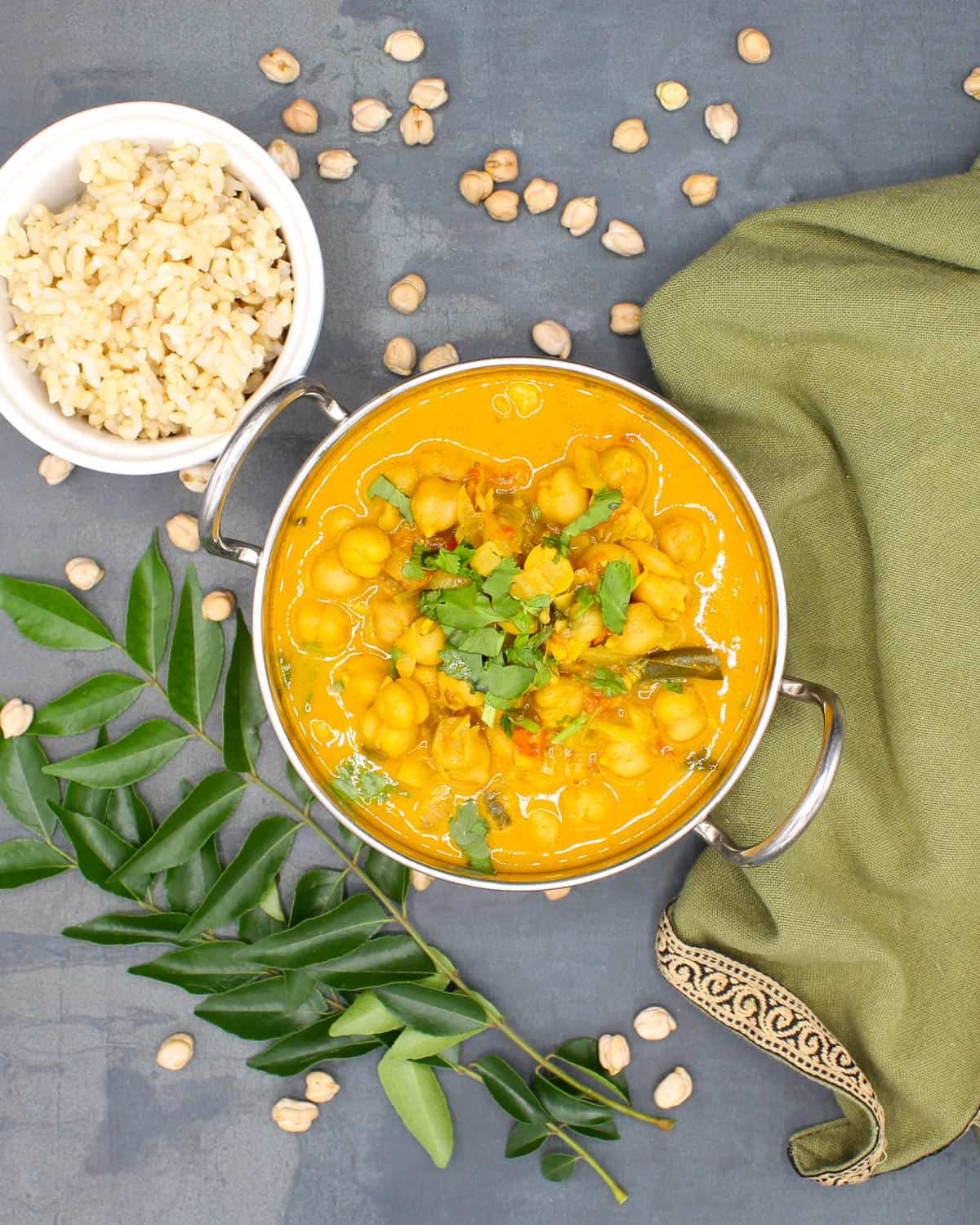 Overhead shot of chickpea curry, south Indian style, in a karahi with brown rice on the side and chickpeas and curry leaves scattered around and a green napkin.