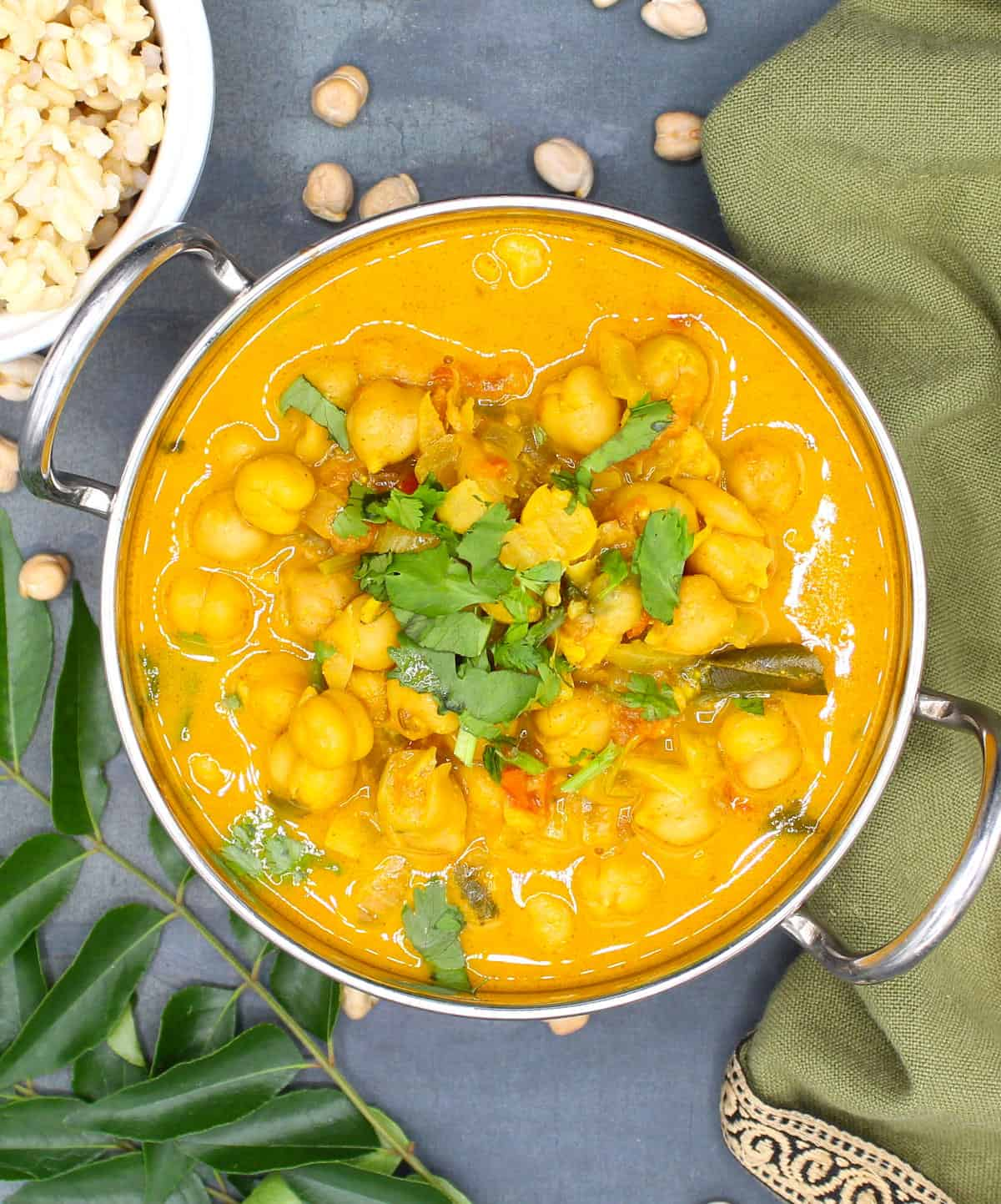 Overhead shot of chickpea curry with coconut milk in a steel karahi with brown rice and curry leaves and chickpeas scattered around.