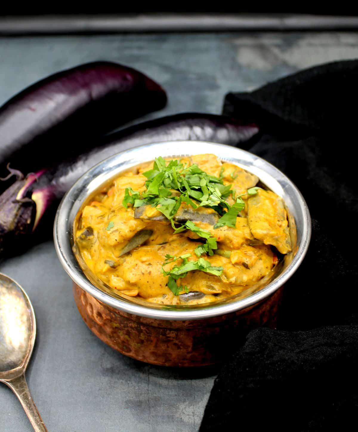 Front photo of vegan dahi baingan with cilantro garnish and eggplants and a steel spoon around it.