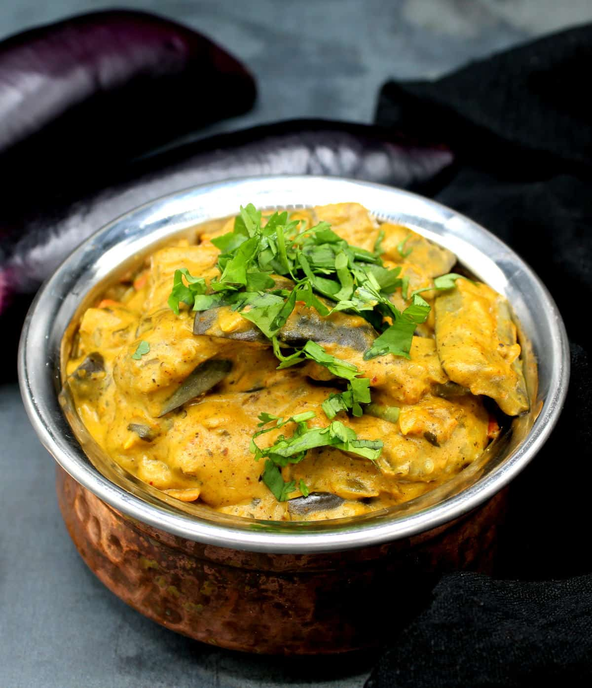 Front photo of vegan dahi baingan in a copper and steel Indian serving bowl with eggplants in background.