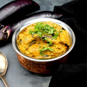 Vegan Dahi Baingan in a copper and steel pot with brinjals in the background and a silver spoon