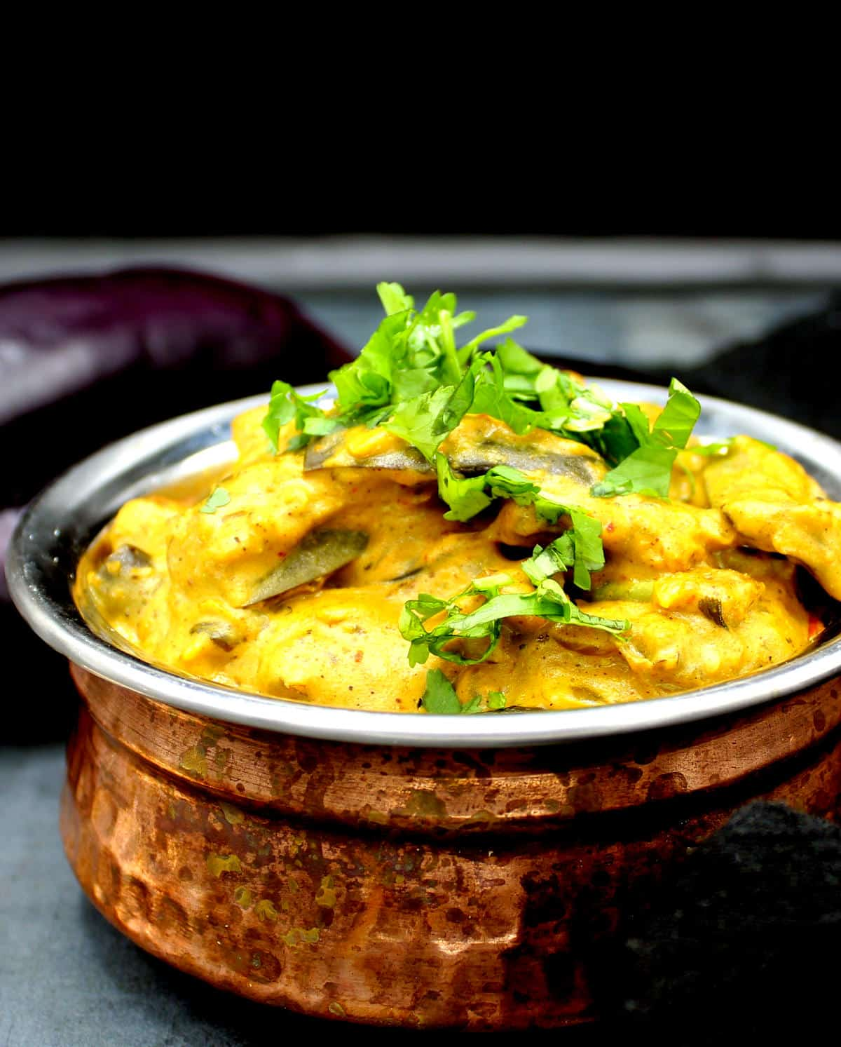 Closeup photo of dahi baingan with vegan yogurt in a copper and steel pot with cilantro and aubergines in background.