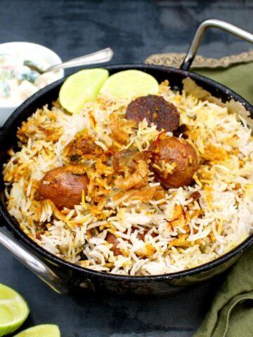 Closeup photo of a kadhai with vegan dum aloo biryani with raita and slices of lime.