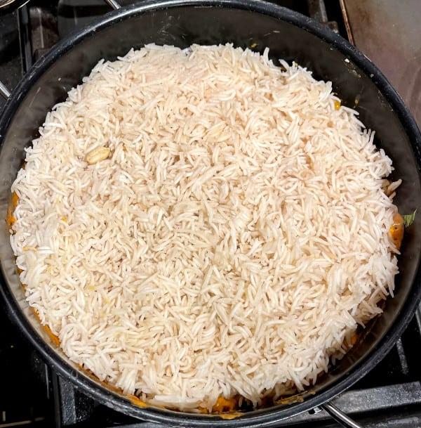Rice layered over dum aloo biryani gravy
