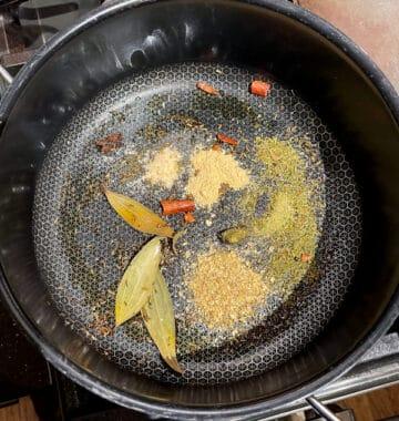 Spices roasting in pot for dum aloo biryani