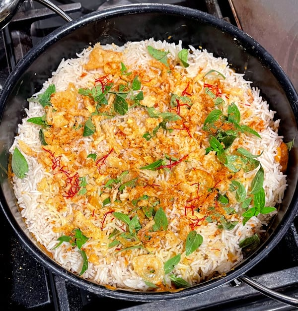 Dum Aloo Biryani in pot with rice layered over the dum aloo gravy and onions, saffron, mint and garam masala sprinkled on top.