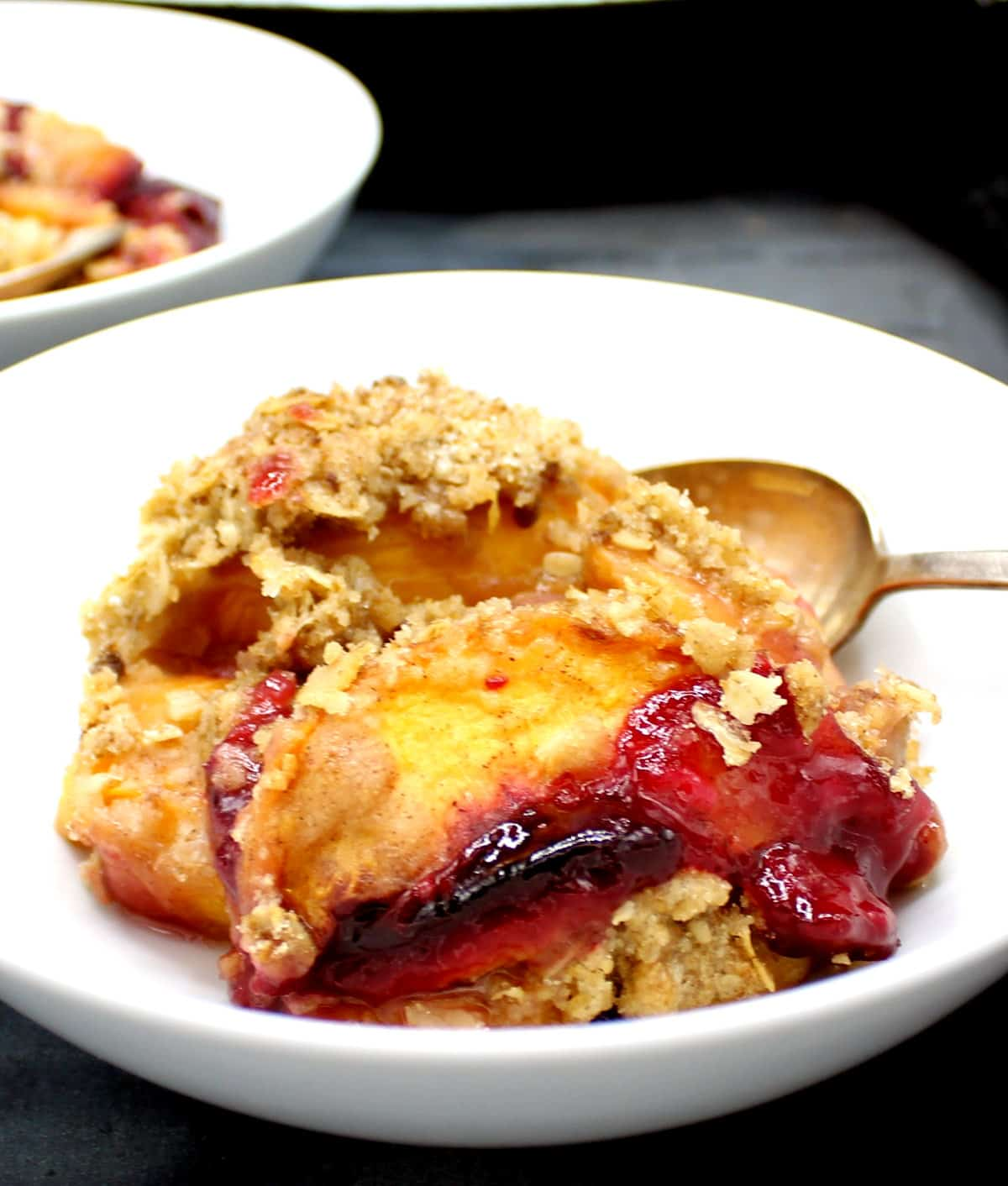 Closeup of vegan plum and peach crisp in a bowl with a spoon.