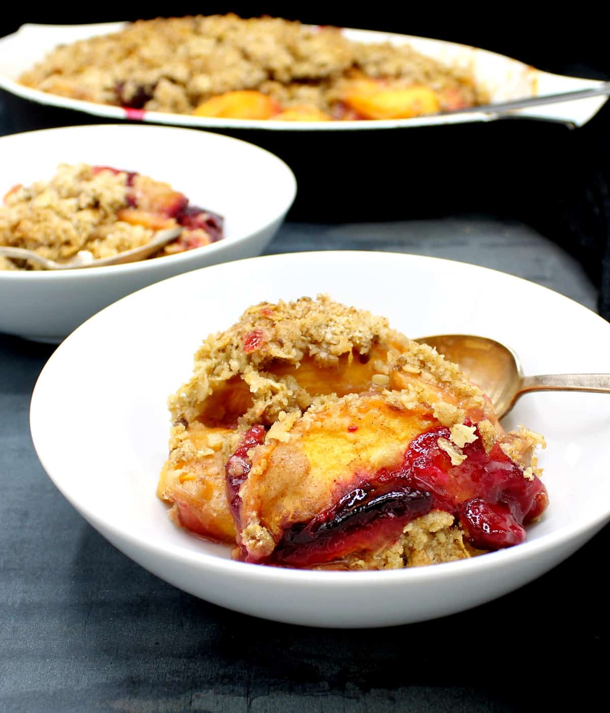 Closeup of a bowl of peach and plum fruit crisp with a spoon.