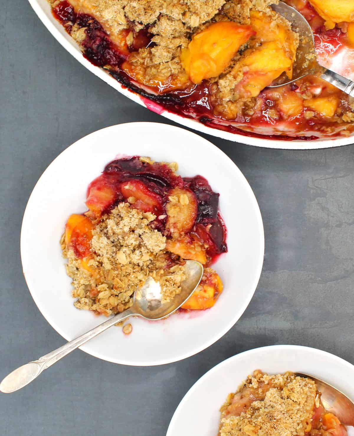 Photo of abowl of delicious vegan peach and plum crisp with a spoon, with the baking dish in the background.