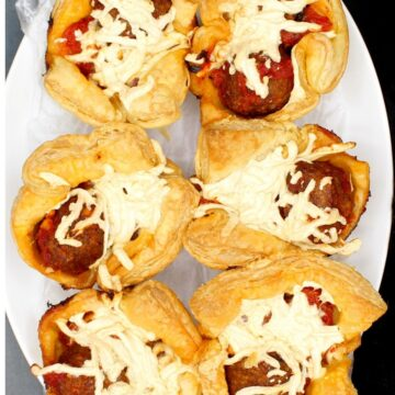 Crispy, golden vegan puff pastry cups with meatball marinara sauce on a white plate.