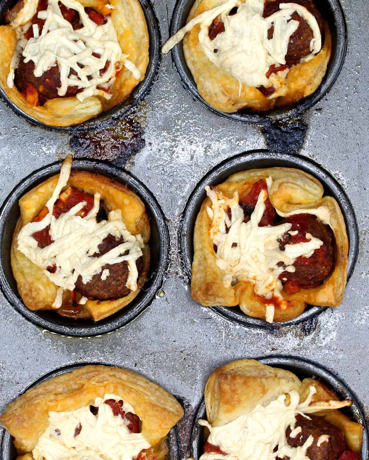 Vegan puff pastry cups with meatballs and marinara sauce and cheese in a muffin tin.