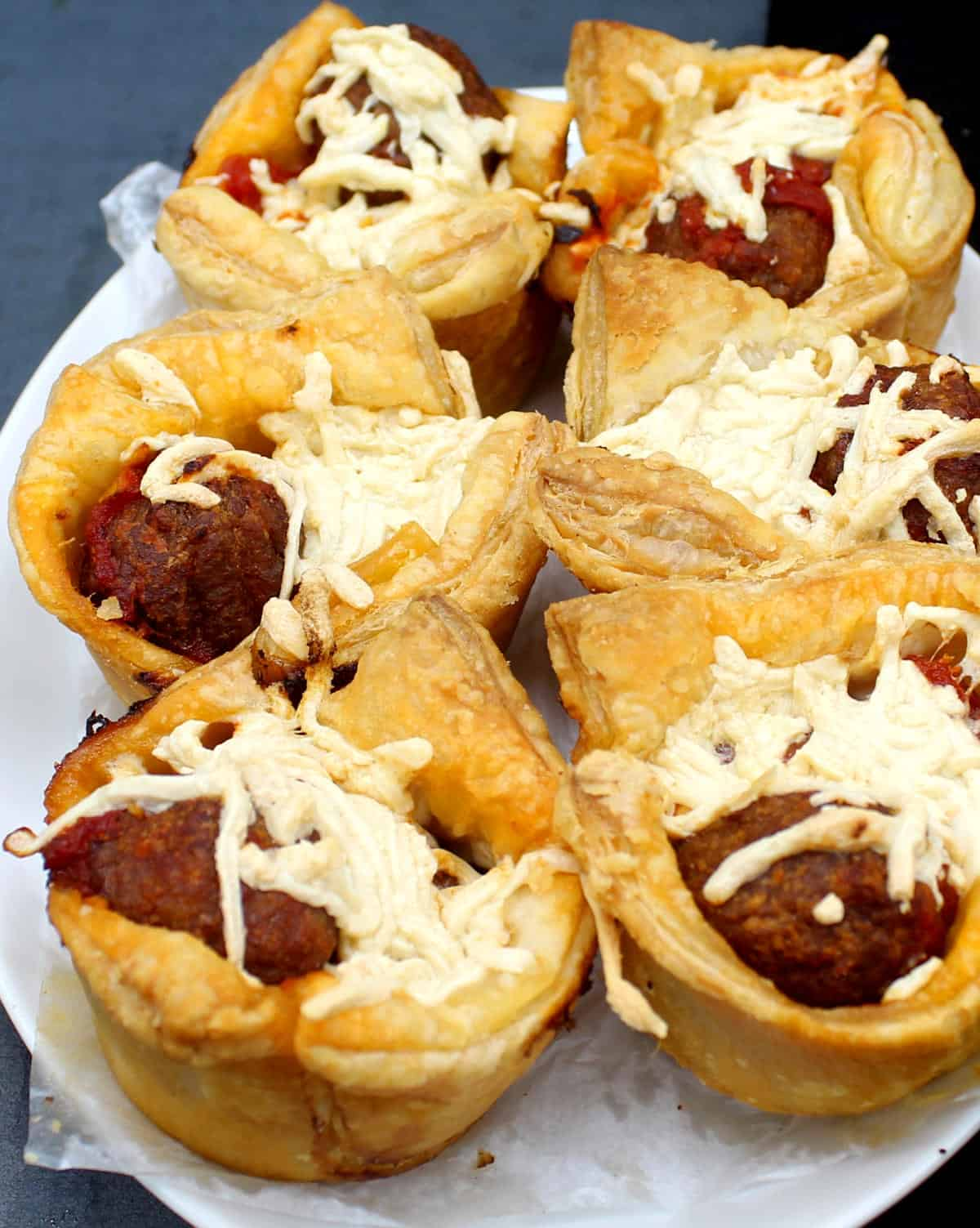 Photo of six vegan puff pastry cups with marinara meatballs and cheese.