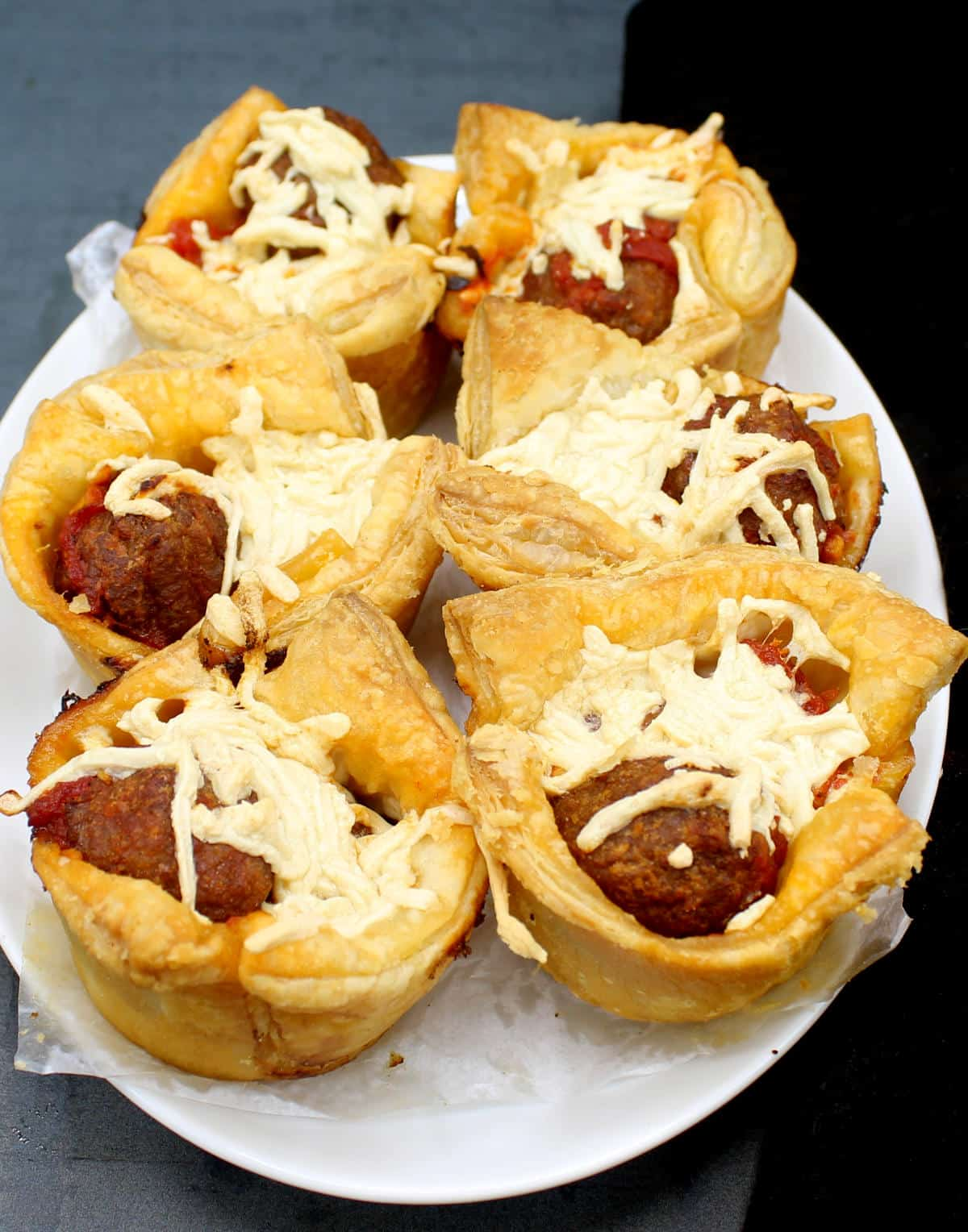 Front photo of six vegan puff pastry cups with marinara meatballs on a white plate.