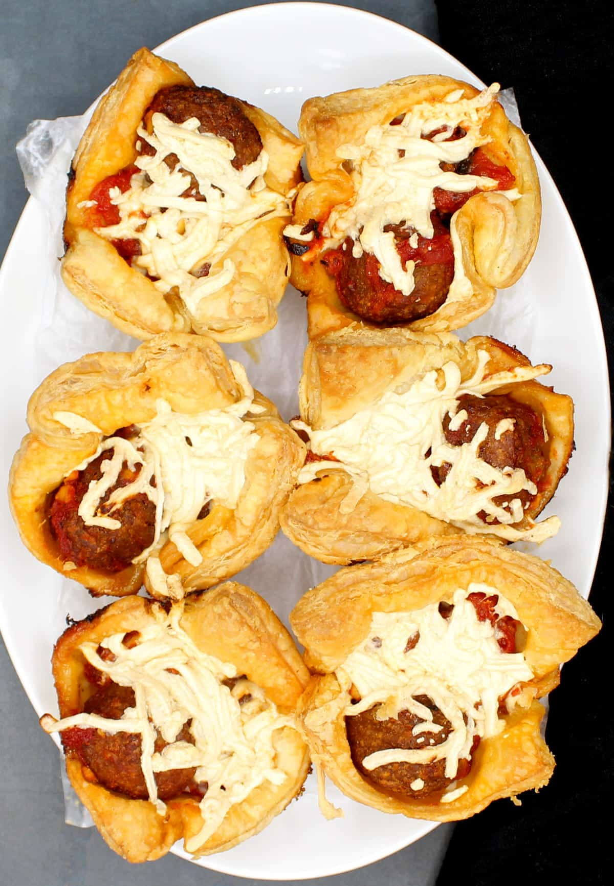 Photo of six vegan puff pastry cups with vegan cheeze and marinara meatballs on an oval white plate.