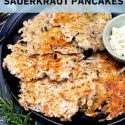 Image of vegan sauerkraut pancakes in black plate with rosemary