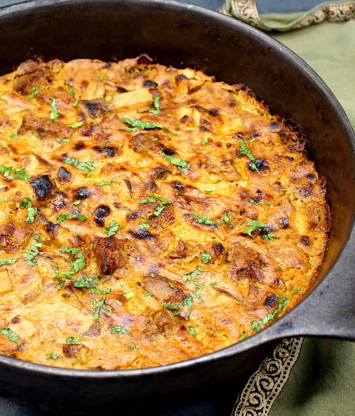 Front closeup of a vegan cheezy breakfast casserole in cast iron skillet with green napkin.