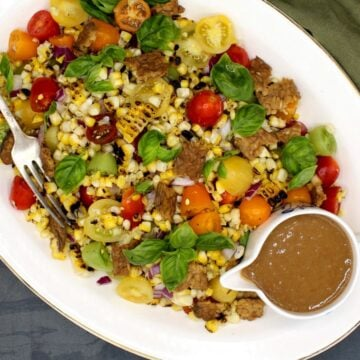 A closeup photo of a large platter of grilled corn salad with cherry tomatoes and basil and a creamy sesame dressing on the side.